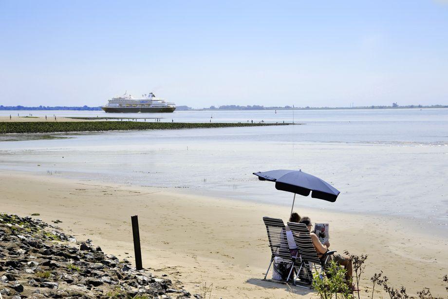 Paar sitzt unter einem Sonnenschirm am Elbstrand und beobachtet Schiff auf der Elbe