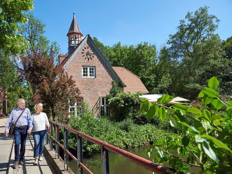Ein älteres Prächen steht auf der Brücke über den Rantzauer See vor einem historischen Gebäude der Schlossinsel Barmstedt