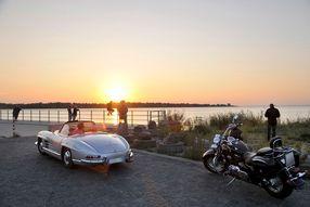 Ein Auto und ein Motorrad am Elbufer bei Sonnenuntergang