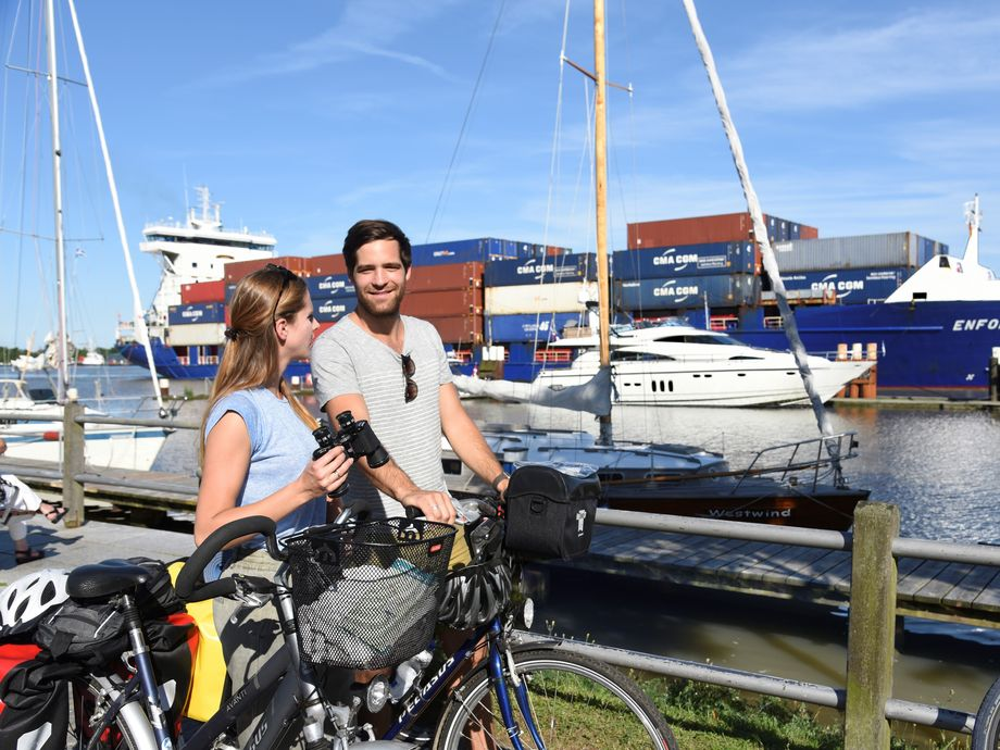 Ein Pärchen auf Fahrrädern steht am Hafen vor einer kleinen Yacht und einem Containerschiff