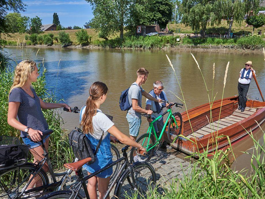 Junge Radfahrer schieben ihr Rad auf eine hölzernde Fähre zum überqueren des Flusses.