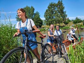 Fünf Personen, zwei davon mit Fahrrad, die vom Bord der kleinen Fähre Kronest gehen