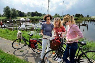 Familie plant Fahrradtour am Bootshafen