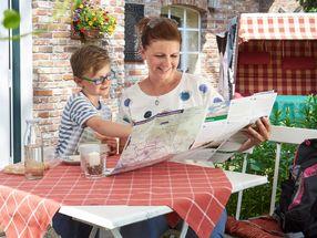 Mutter und Kind lesen Prospekt zu Hause auf der Terasse
