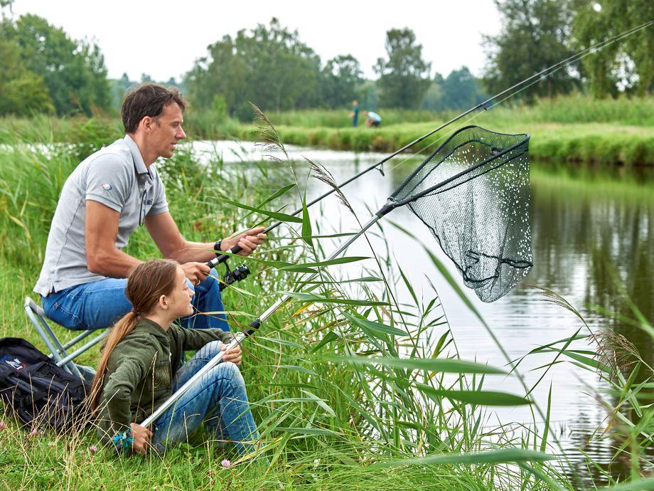 Angler mit Netz am Fluss