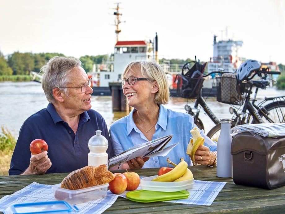 Ehepaar genießt Picknick an der Brunsbütteler Schleuse, im Hintergrund die Kanalfähre