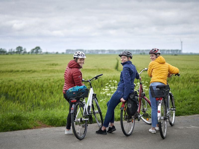 Drei Radfahrerinnen machen Pause vor einem Feld