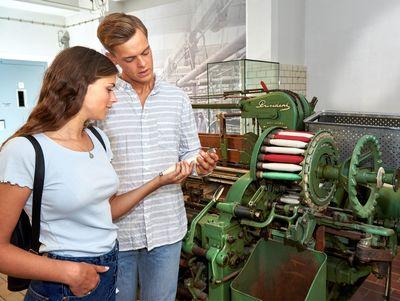 Zwei Leute betrachten alte Maschine im Industriemusuem Elmshorn
