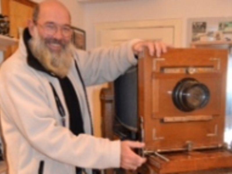 Das Bild zeigt den Leiter des Kameramuseums in Beidenfleth vor einem historischem Fotoapparat.