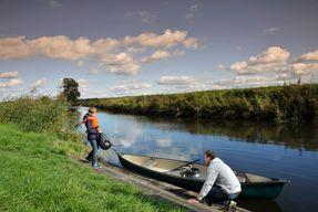 Ein Kanu am Ufer eines Fluss und zwei Personen die daraus aussteigen
