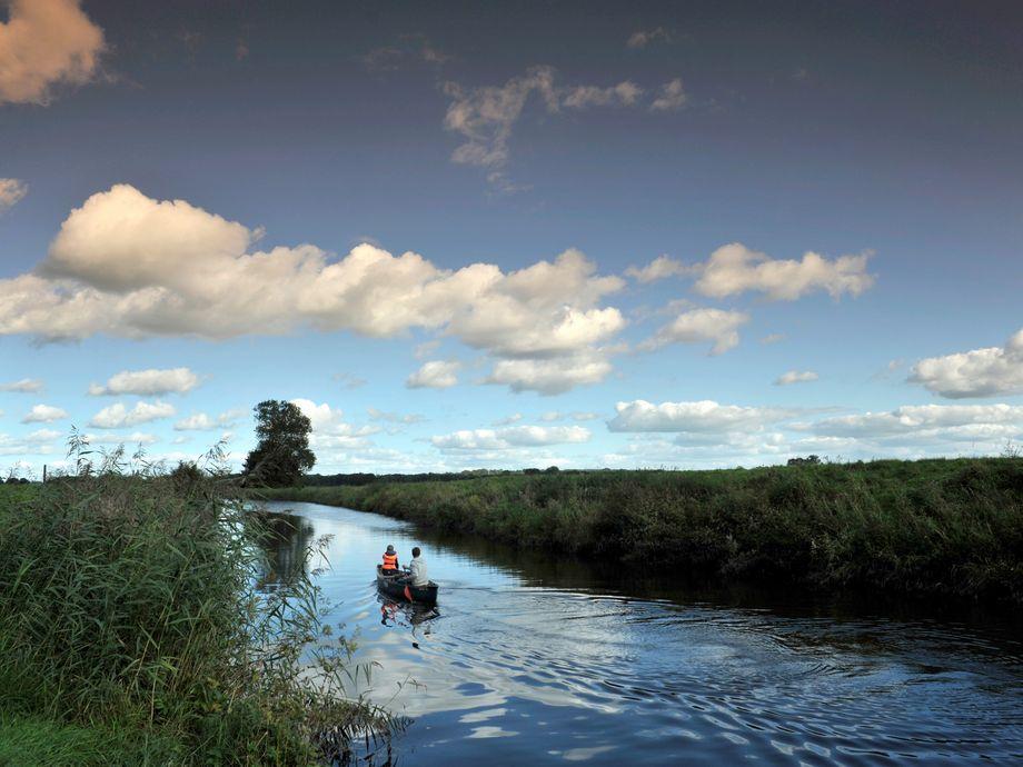 Vater und Sohn fahren Kanu auf der Stör mit weiten Feldern link und rechts