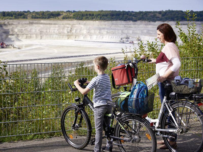 Mutter und Kind stehen auf Fahrrädern vor einer gewaltigen Grube in der Kreide abgebaut wird