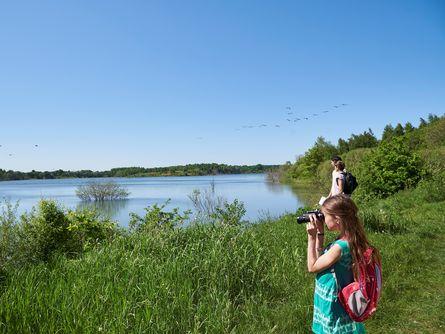 Mädchen mit Fernglas blickt auf die Landschaft mit Fluss