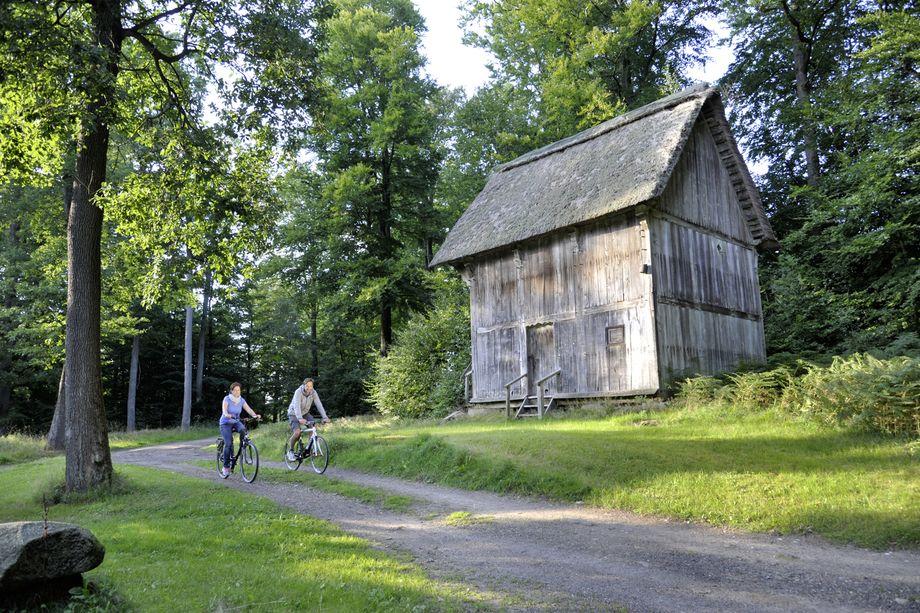 Zwei Fahrradfahrer vor einer großen alten Scheune im Naturpark Aukrug
