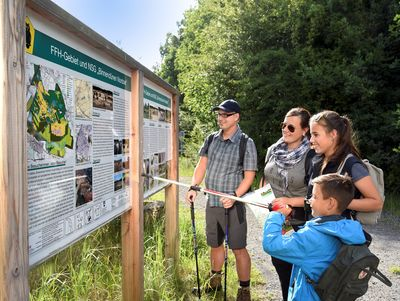 Familie liest Informationstafel in der Nordoer Heide