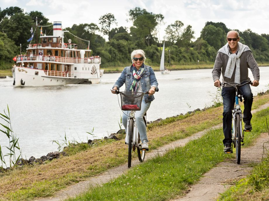 Zwei Radfahrer fahren am Nord Ostsee Kanal entlang