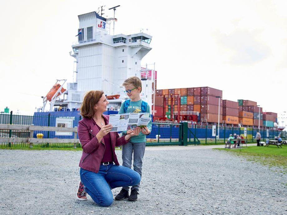 Mutter mit Kind schauen auf eine Regionskarte mit einem Containerschiff im Hintergrund