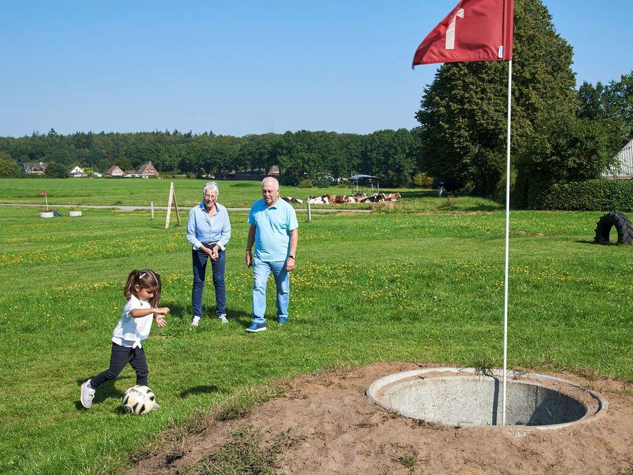 Eine Ehepaar mit Enkel spielt Minigolf mit einem Fußball
