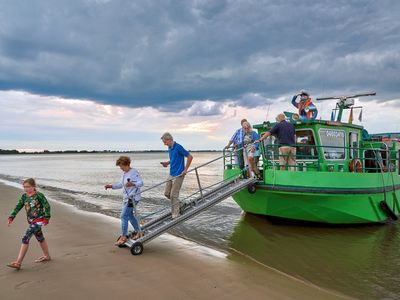 Gruppe von Leuten gehen vom Tiedenkieker auf den Strand