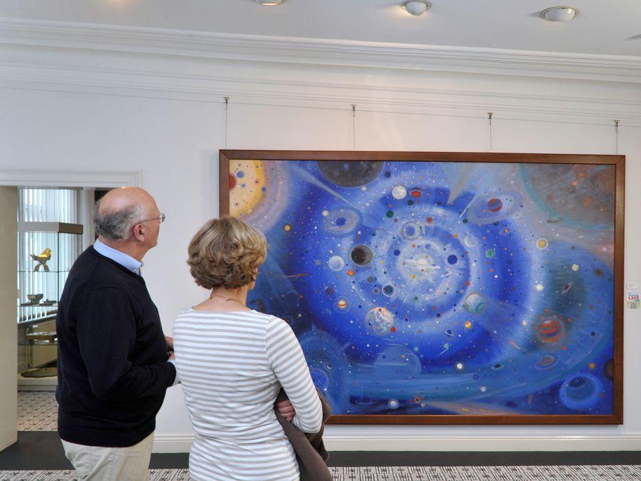 Ein älteres Paar steht vor einem Gemälde von Wenzel-Hablik im Museum