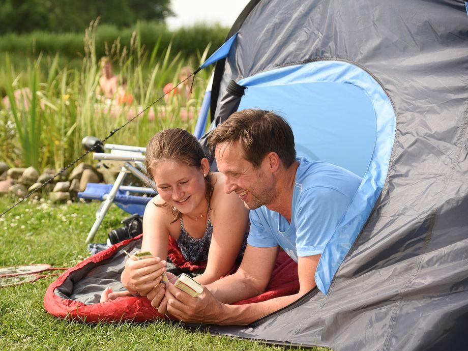 Vater und Tochter sitzen im Zelt und Spielen ein Quiz