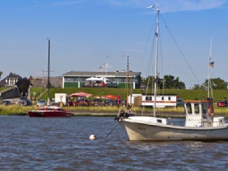 Ein Boot auf ruhiger See, im Hintergrund das Fährhaus Kollmar.