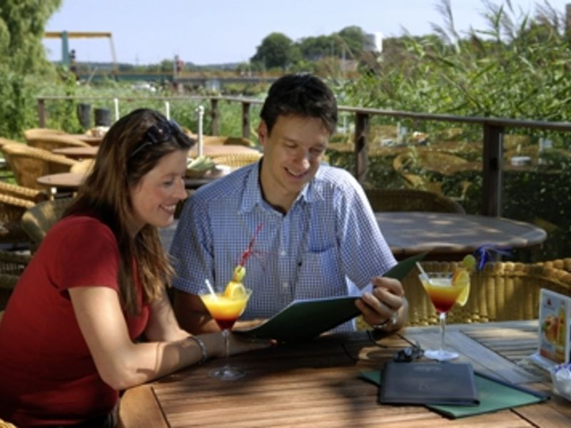 Zwei Menschen sitzen am Tisch und trinken Cocktails während Sie eine Speisekarte lesen.