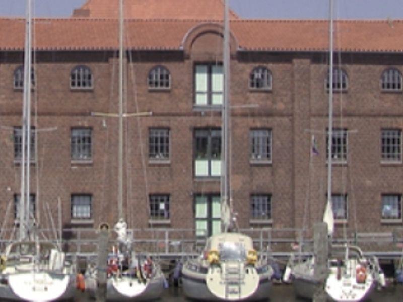 """Mehrer Schiffe angedockt vor einem großen Gebäude, dem Restaurant """"Zur Alten Mühle"""""""